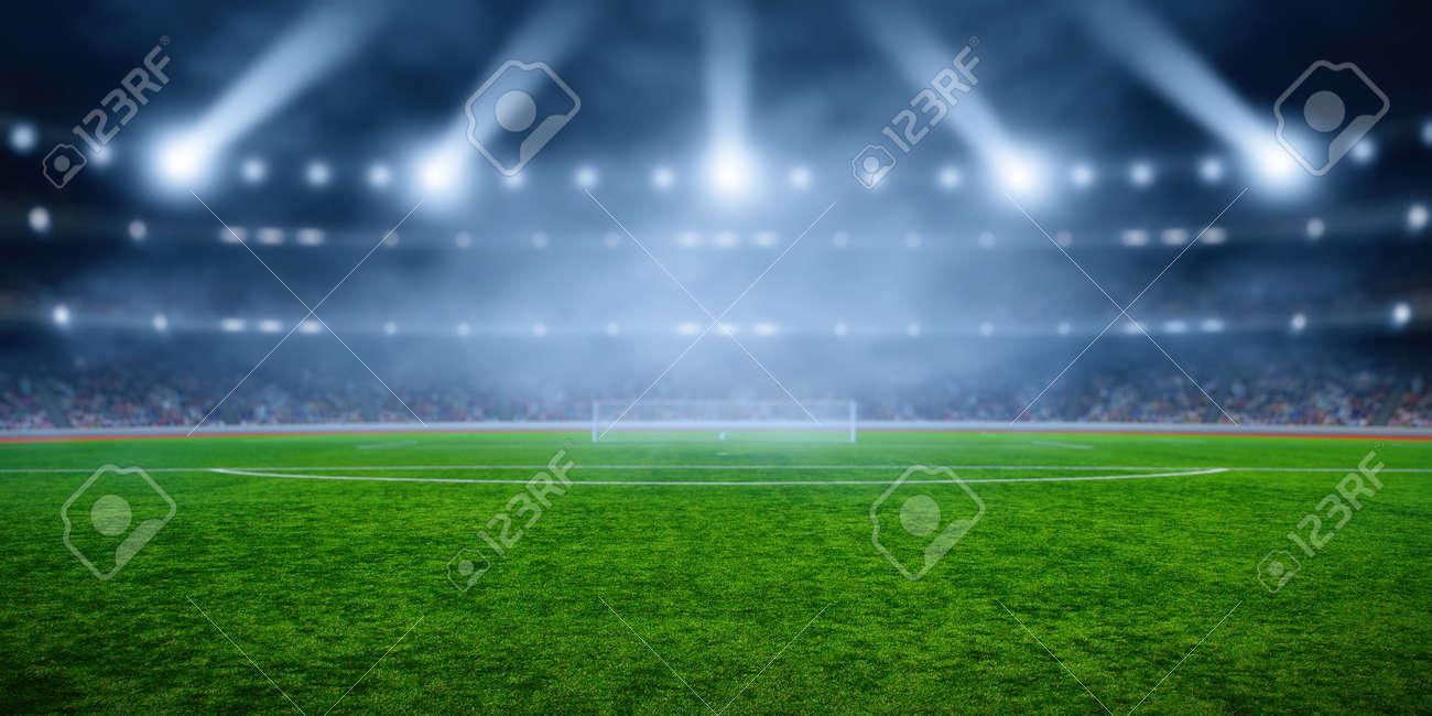 Soccer stadium with illumination, green grass and night blurred sky - 137486571