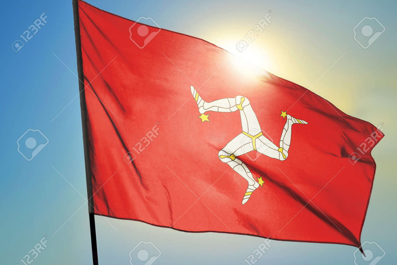 Isle of Mann flag waving on the wind in front of sun - 166480079