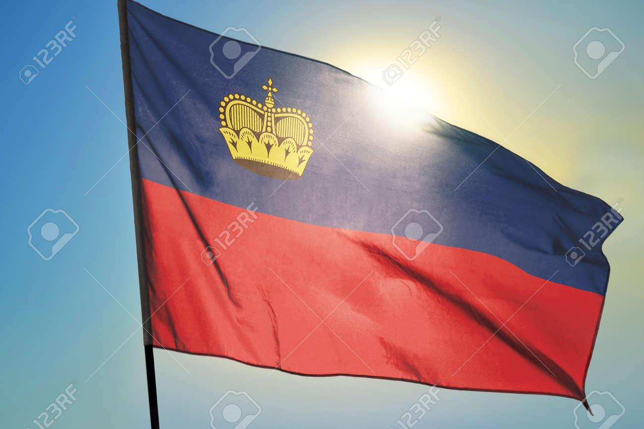 Liechtenstein flag waving on the wind in front of sun - 166480096