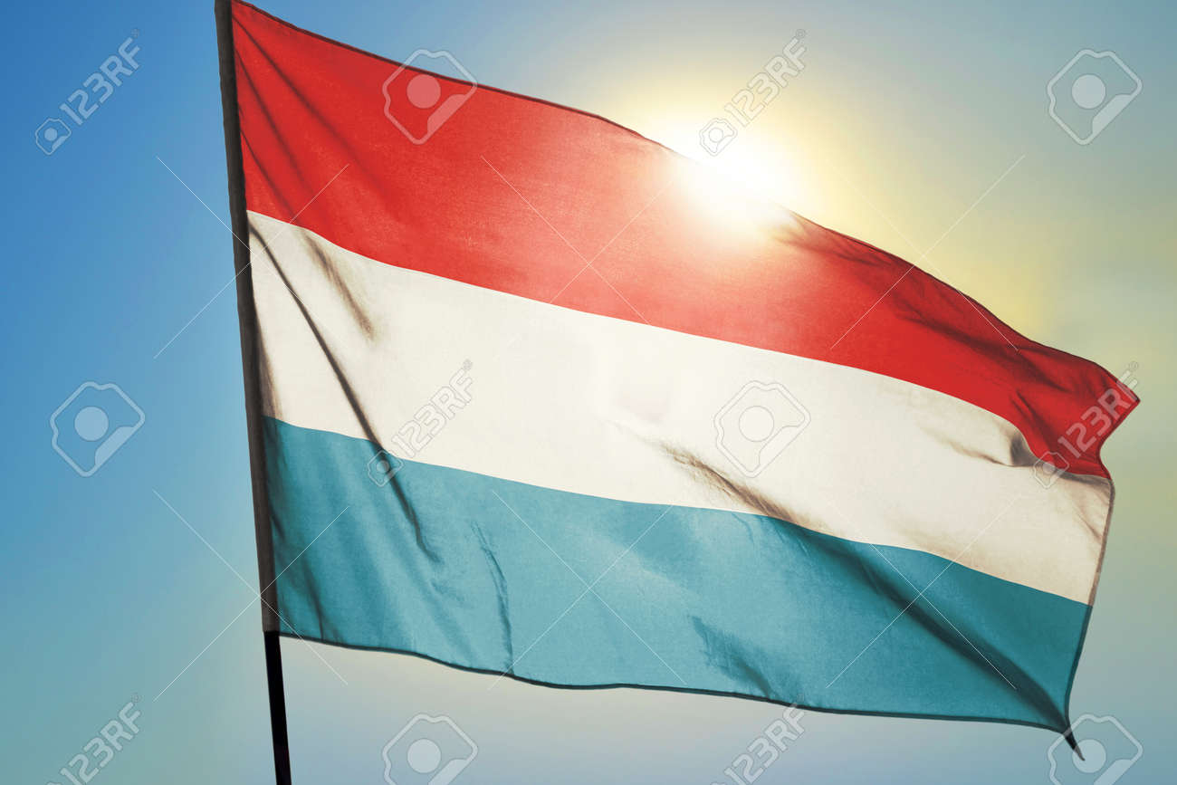 Luxembourg flag waving on the wind in front of sun - 166480098