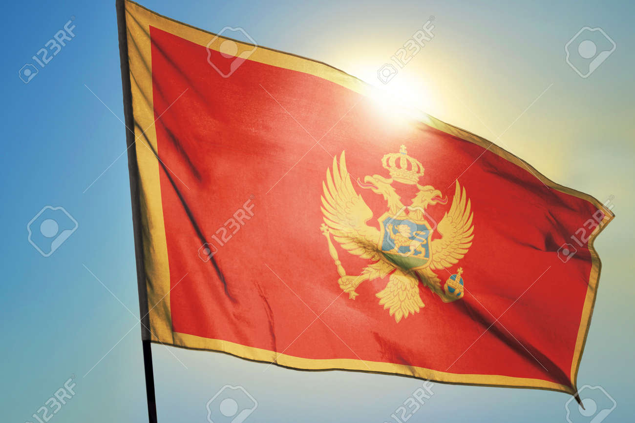 Montenegro flag waving on the wind in front of sun - 166480112