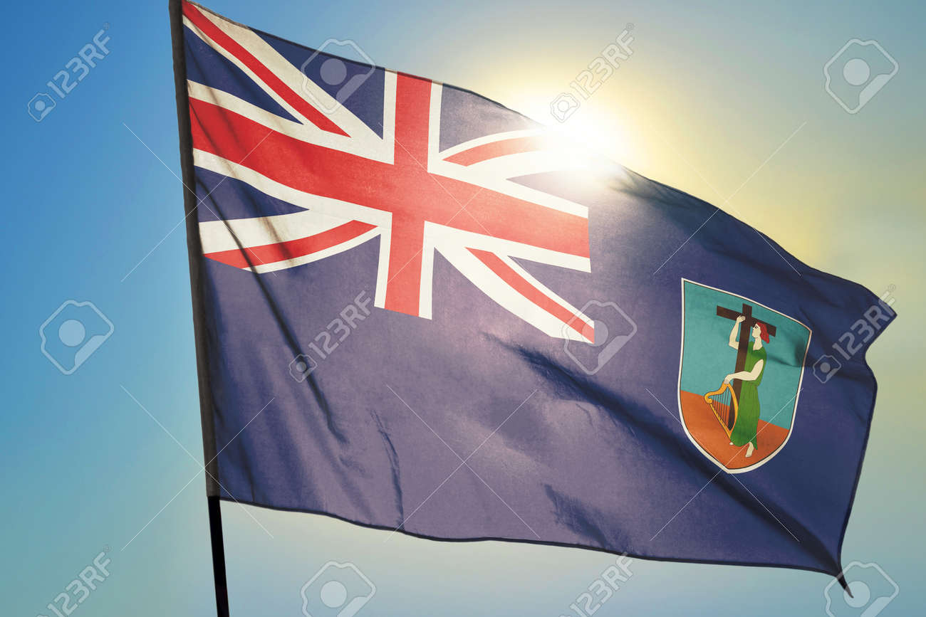Montserrat flag waving on the wind in front of sun - 166480113
