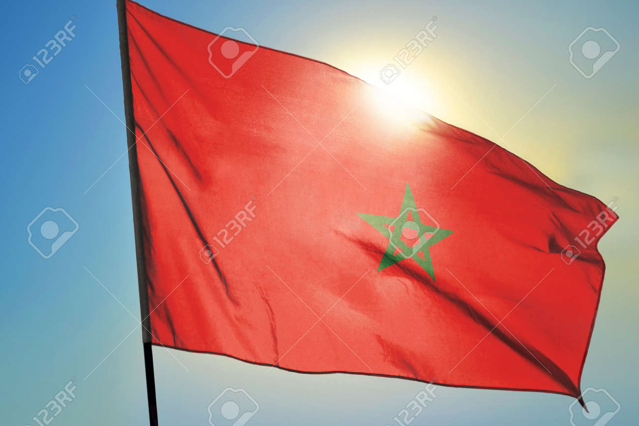 Morocco flag waving on the wind in front of sun - 166480114