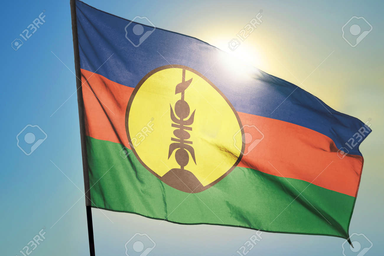 New Caledonia flag waving on the wind in front of sun - 166480119