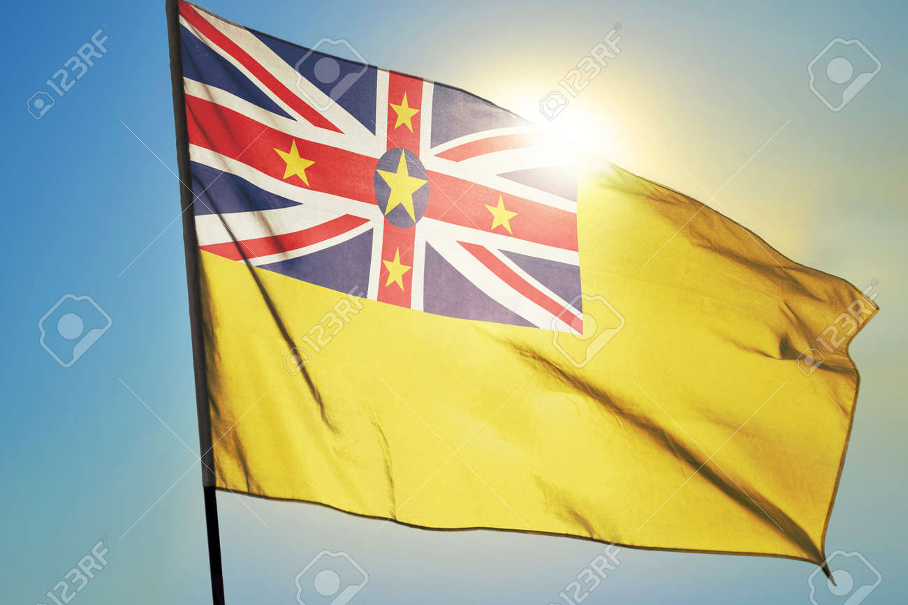 Niue flag waving on the wind in front of sun - 166480122