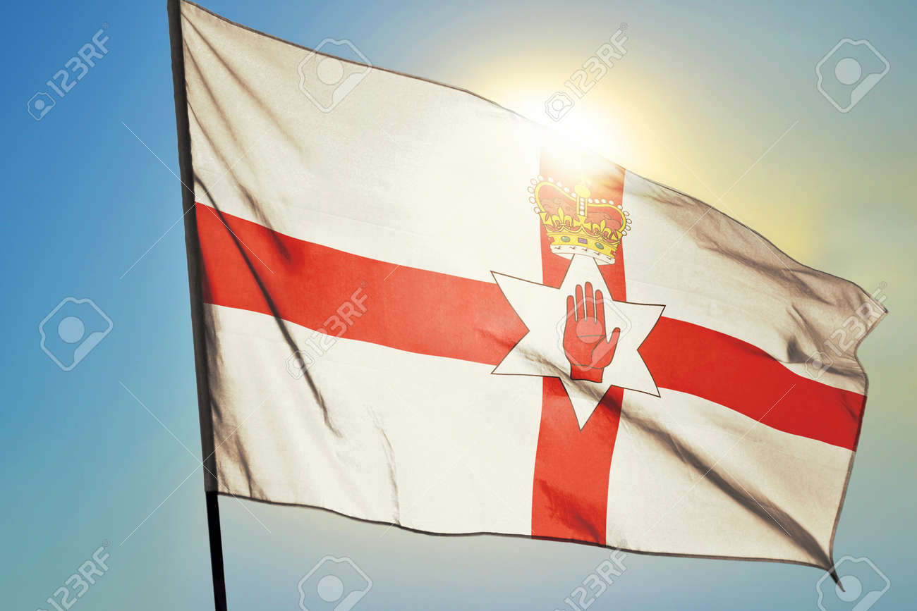 Northern Ireland flag waving on the wind in front of sun - 166480124
