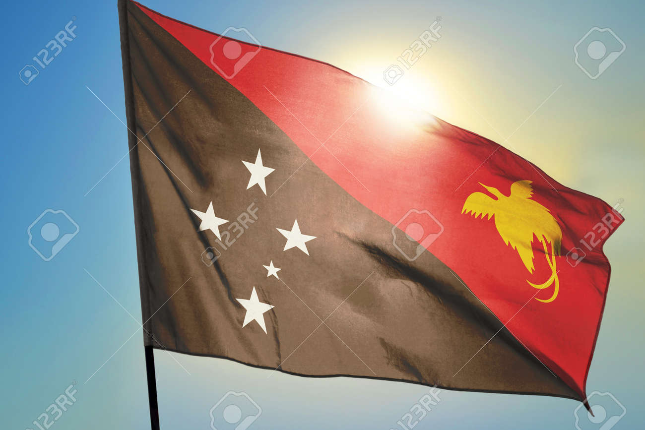 Papua New Guinea flag waving on the wind in front of sun - 166480128