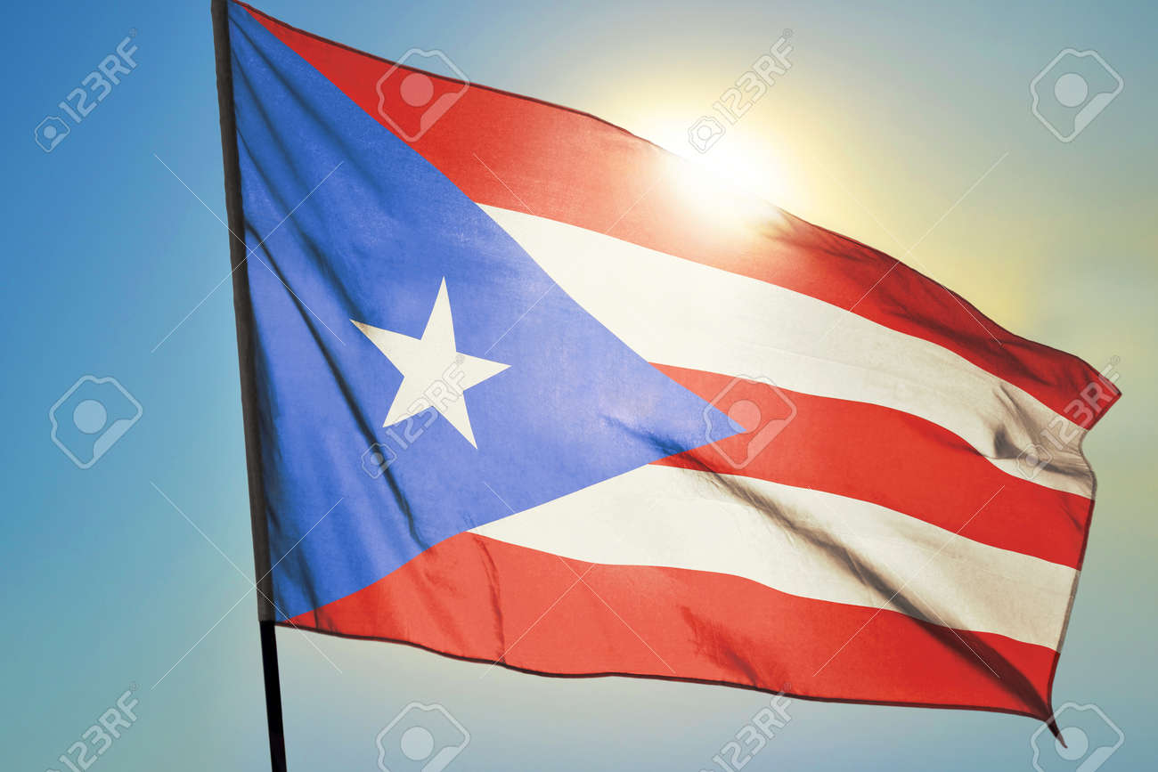 Puerto Rico flag waving on the wind in front of sun - 166480131