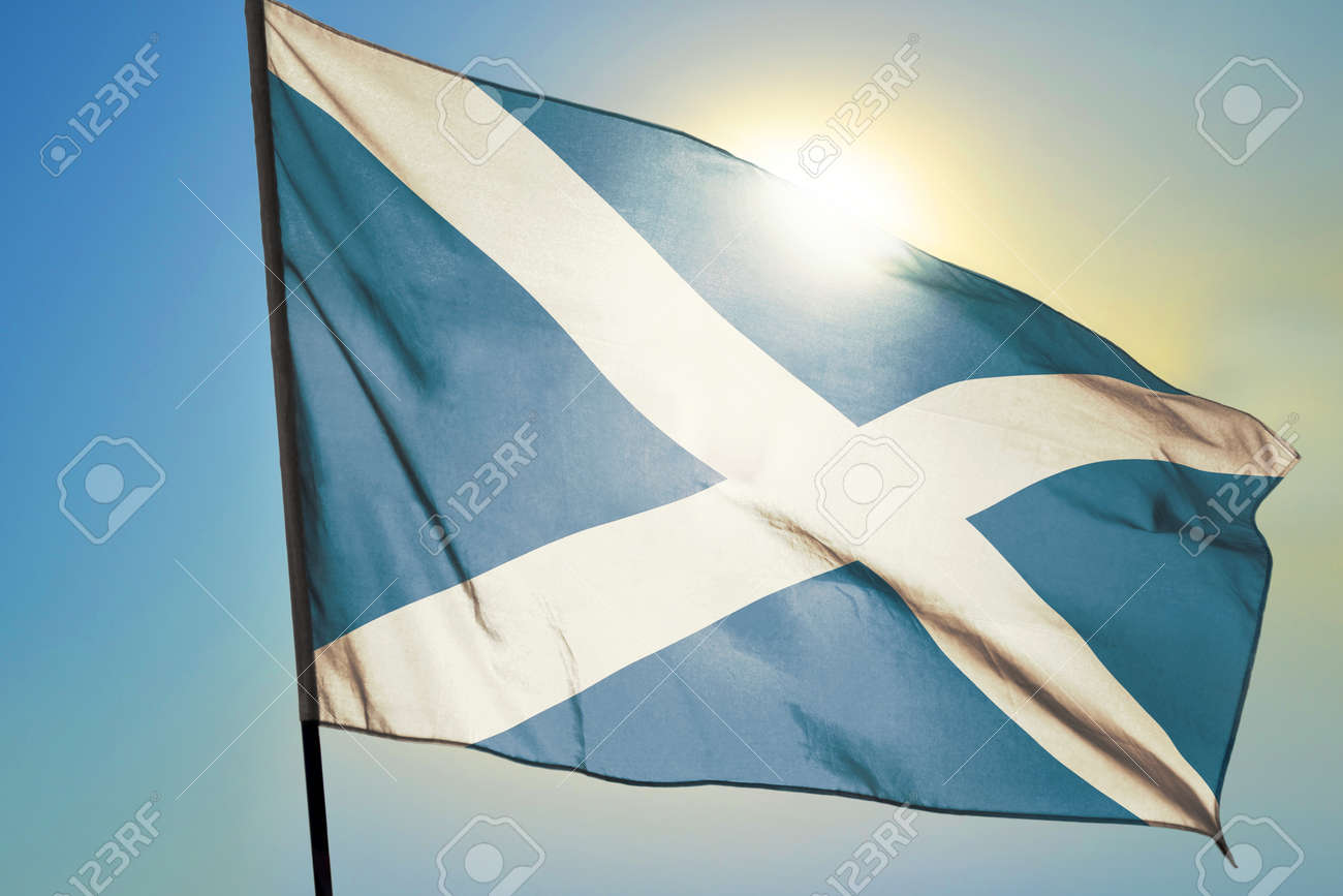 Scotland flag waving on the wind in front of sun - 166480140