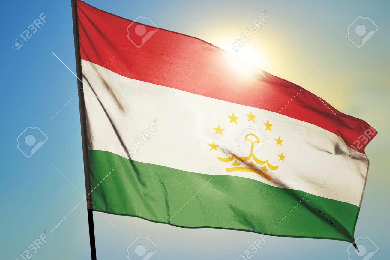 Tajikistan flag waving on the wind in front of sun - 166480152