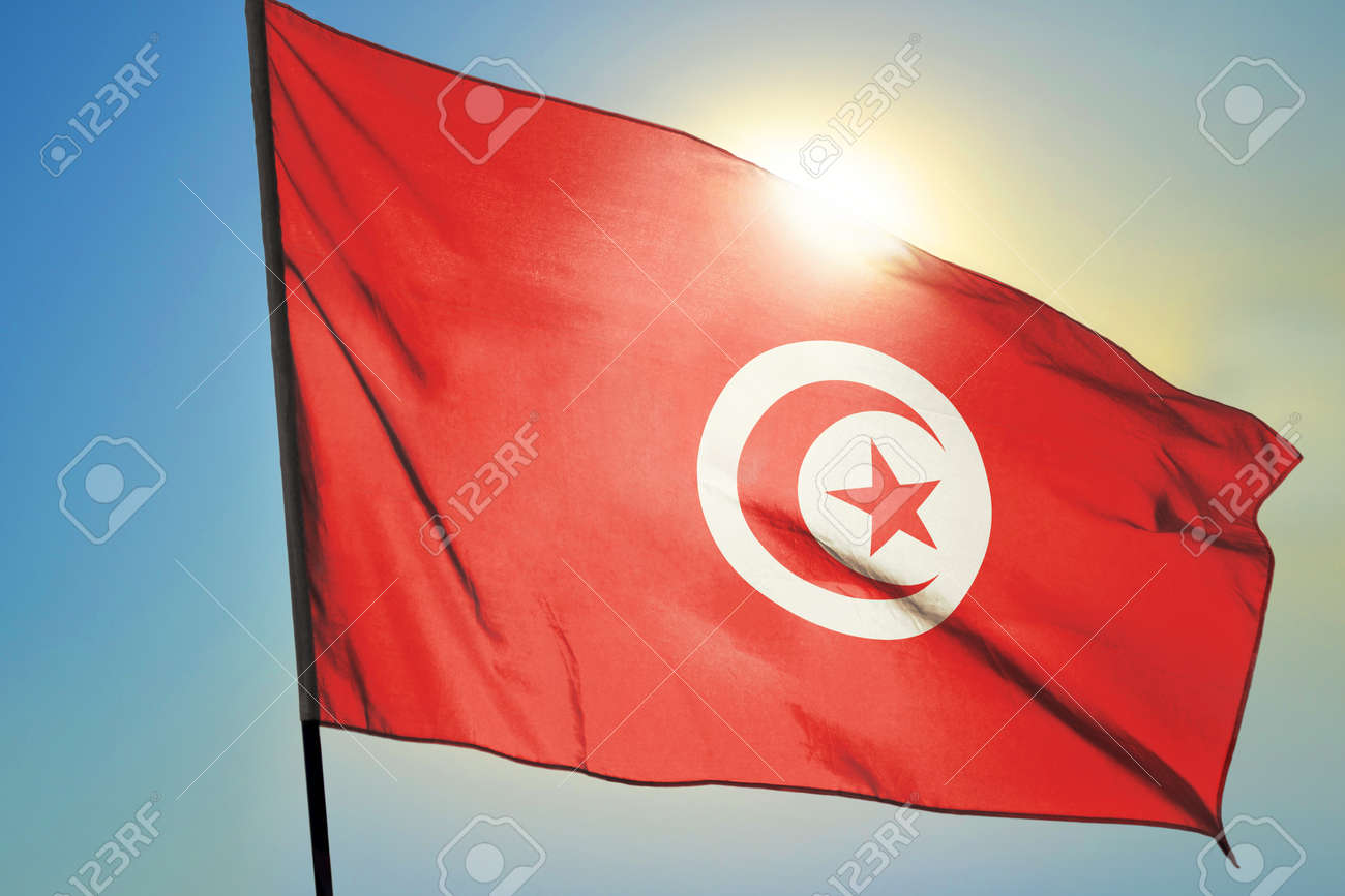 Tunisia flag waving on the wind in front of sun - 166480156