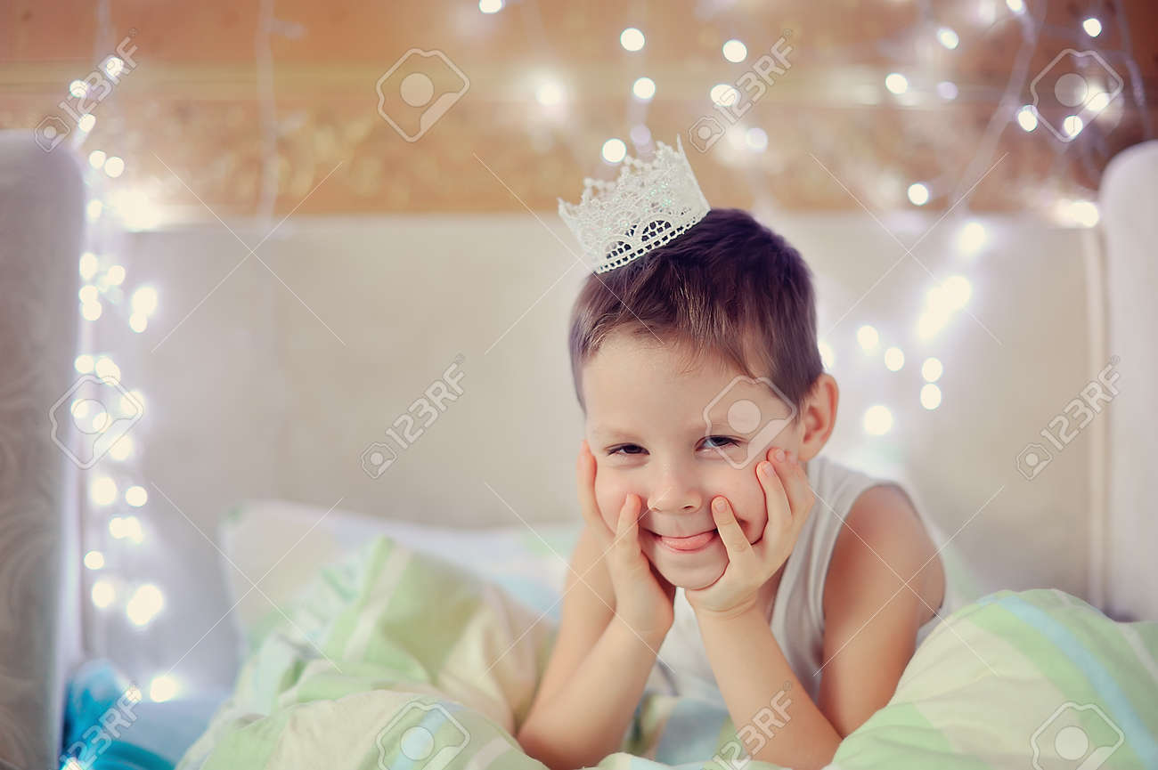 the boy woke up and is sitting in bed with a crown on his head Stock Photo - 16898770