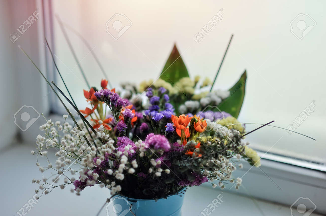 against the window of the small bouquet of colorful flowers in a blue Stock Photo - 17780254