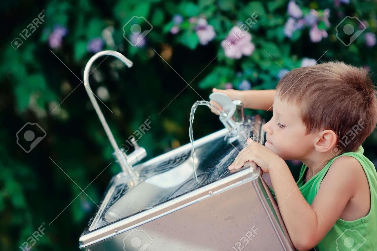little boy reaching for the tap water in the street to get a drink of water Stock Photo - 18160937