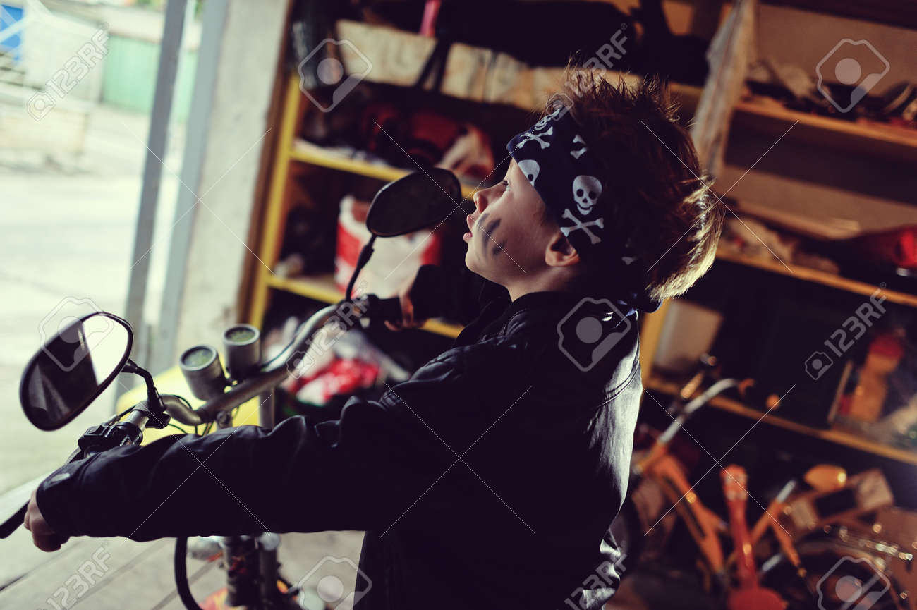 in the garage of a boy in a black jacket with a dirty face on a moped Stock Photo - 22181940