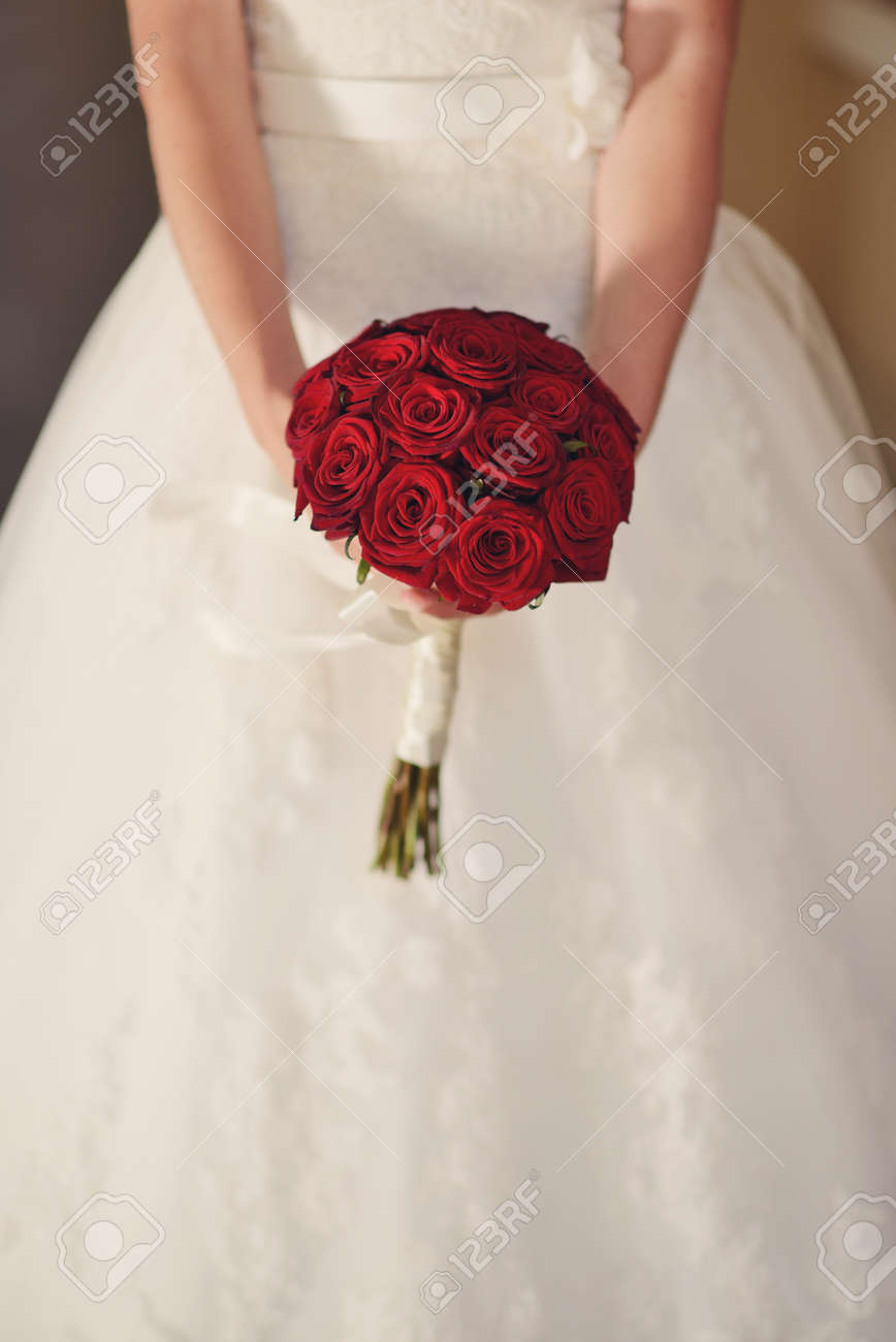 Red And White Wedding.In White Wedding Dress The Bride Holding A Bouquet Of Red Roses