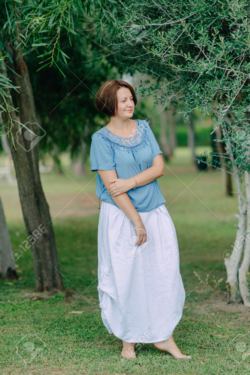 b48ebb77b En el parque bajo un árbol que presenta una mujer en una falda blanca y una  chaqueta azul