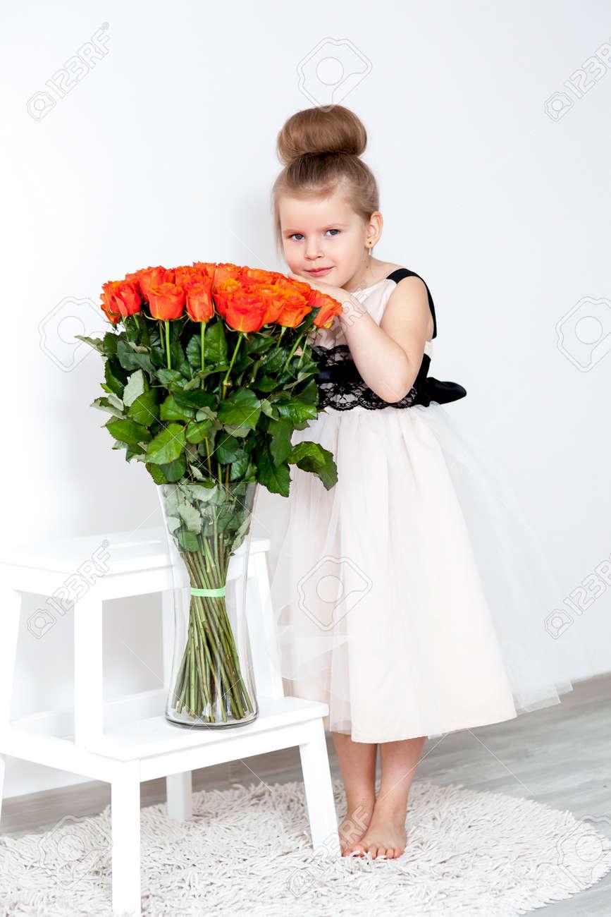 the latest b9a30 5c947 Bella ragazza in abito elegante con un mazzo di rose arancio