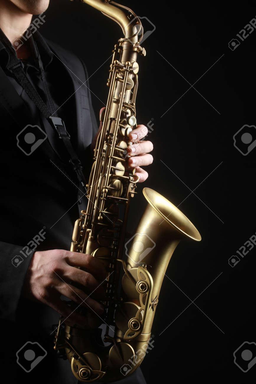Saxophone classical music instruments Saxophonist with alto sax closeup on black Standard-Bild - 34621364