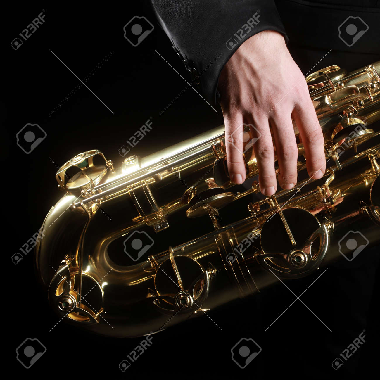 Saxophone jazz music instruments details. Baritone sax with hand of saxophonist closeup on black Standard-Bild - 34621365