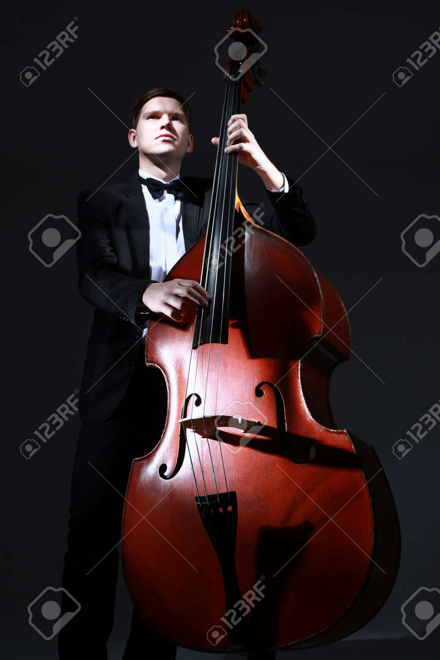 Double bass player contrabass. Classical musician jazz bass acoustic playing  Stock Photo - 88438700 18d18fd20838