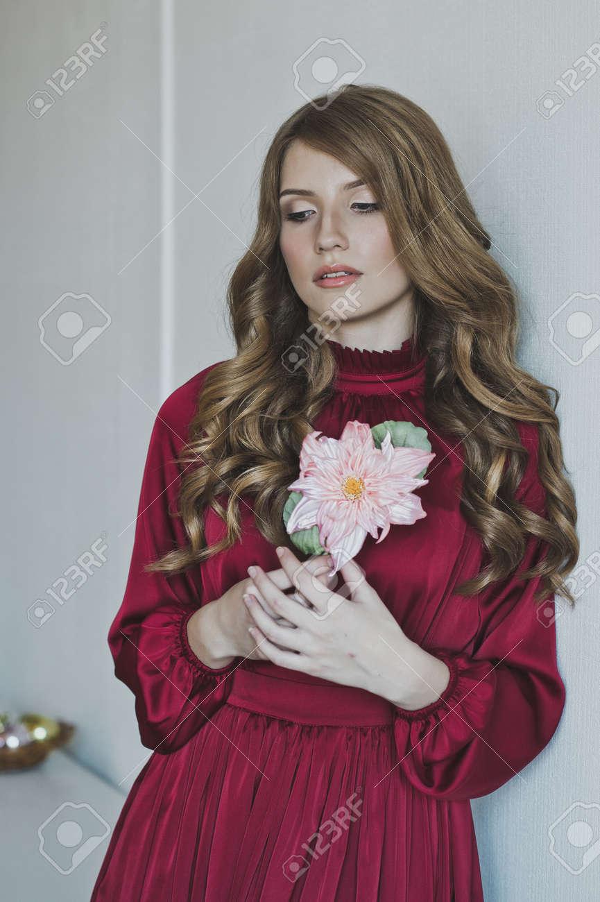 b3f44698efc252 Portret van een meisje in een rode jurk met een rode bloem. Stockfoto -  51096871
