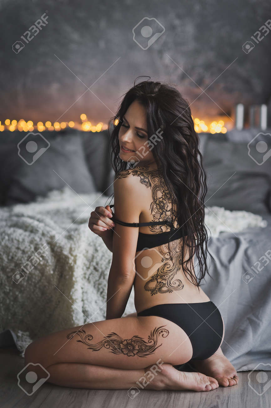 2f63290bf19e Portrait of a beautiful girl in her underwear sitting on the floor by the  bed girl