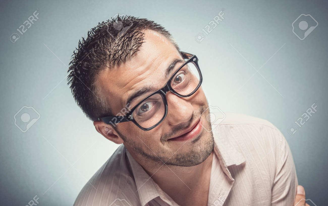 Funny man looking to you. Nerd guy with eyeglasses watching, Dark gray background. Studio shot - 165199544