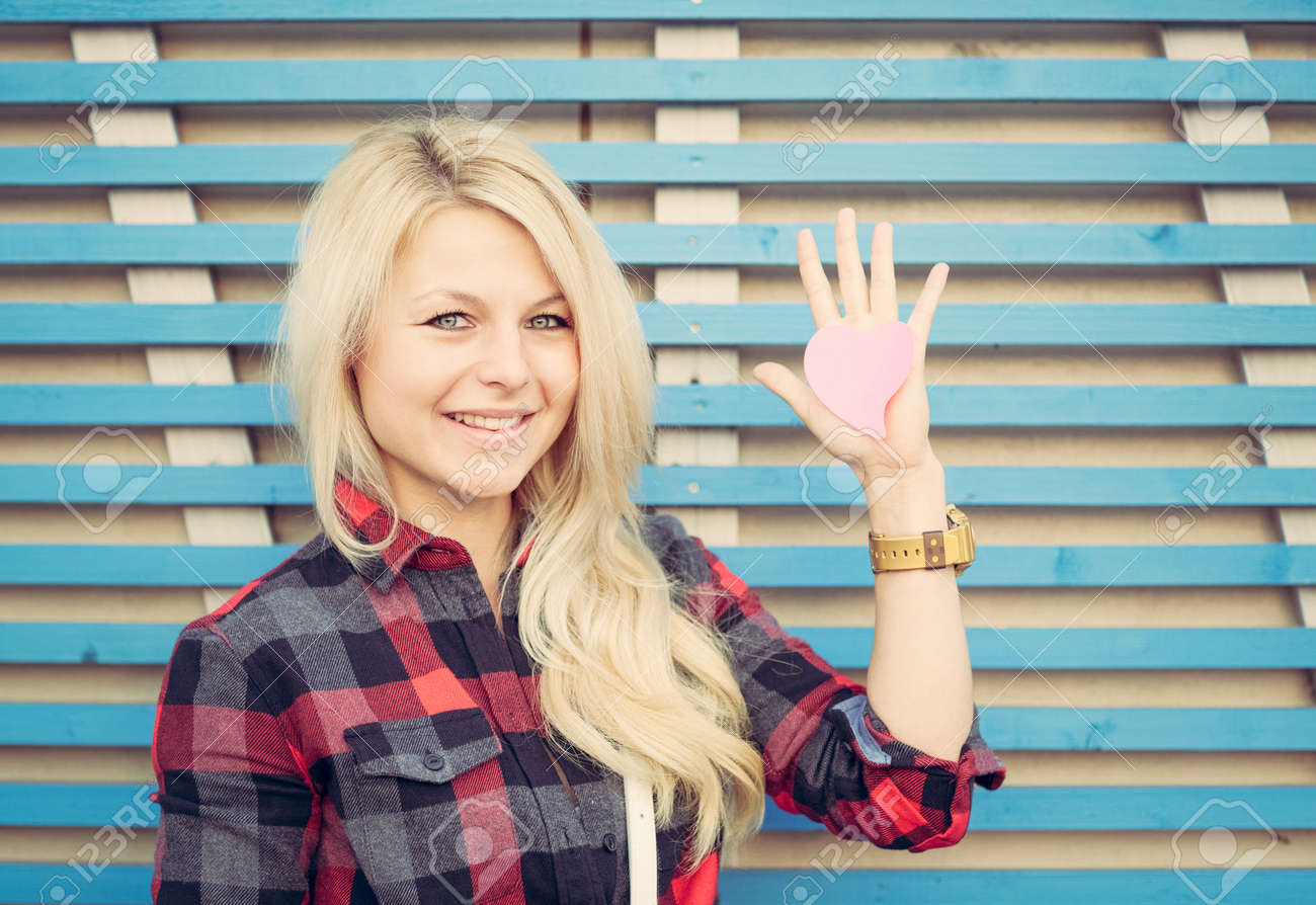 Beautiful girl near the wall on the street in the summer on stock beautiful girl near the wall on the street in the summer on a raised hand voltagebd Images