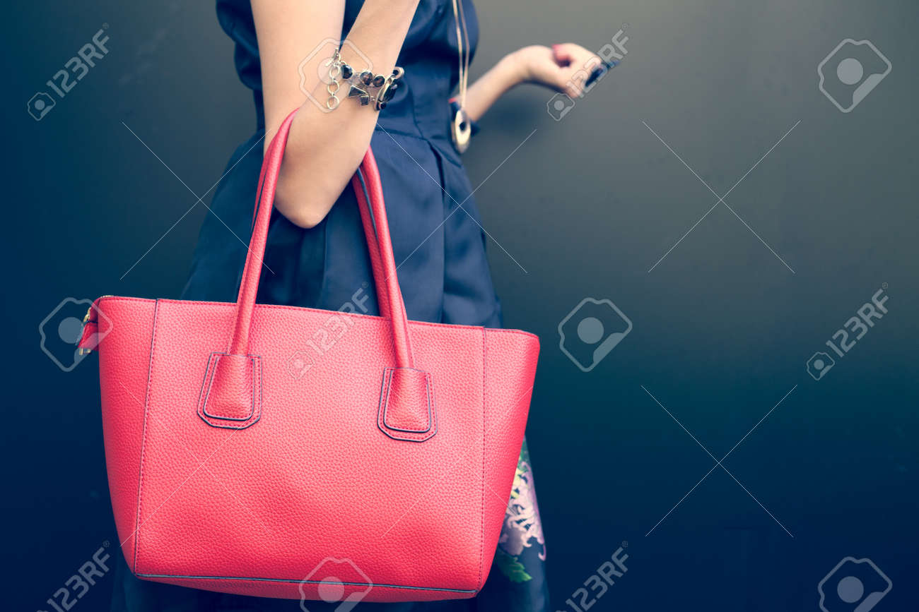 Fashionable beautiful big red handbag on the arm of the girl in a fashionable black dress, posing near the wall on a warm summer night. Warm color Stock Photo - 46047456