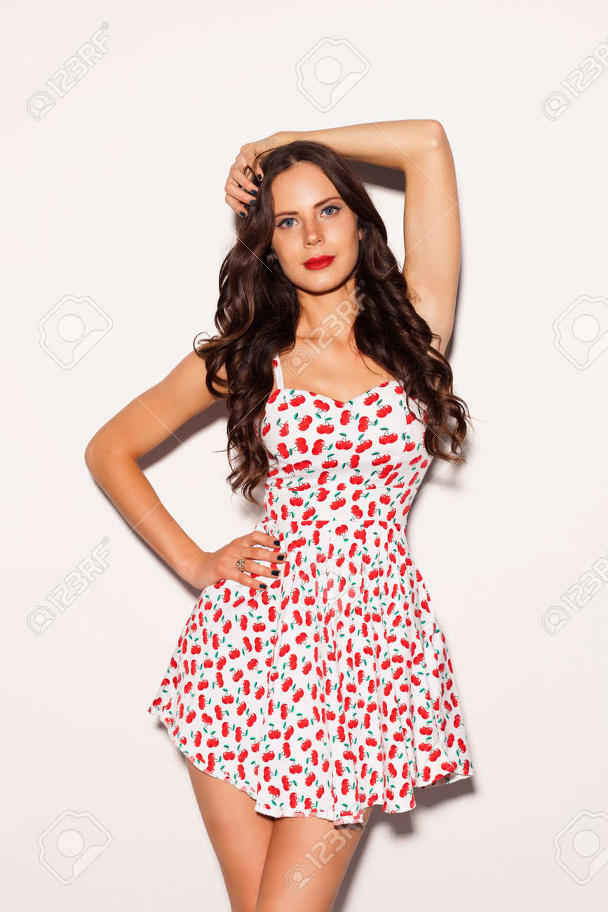 13ff03032b4 Beautiful brunette girl with long hair and blue eyes posing in bright summer  short dress on