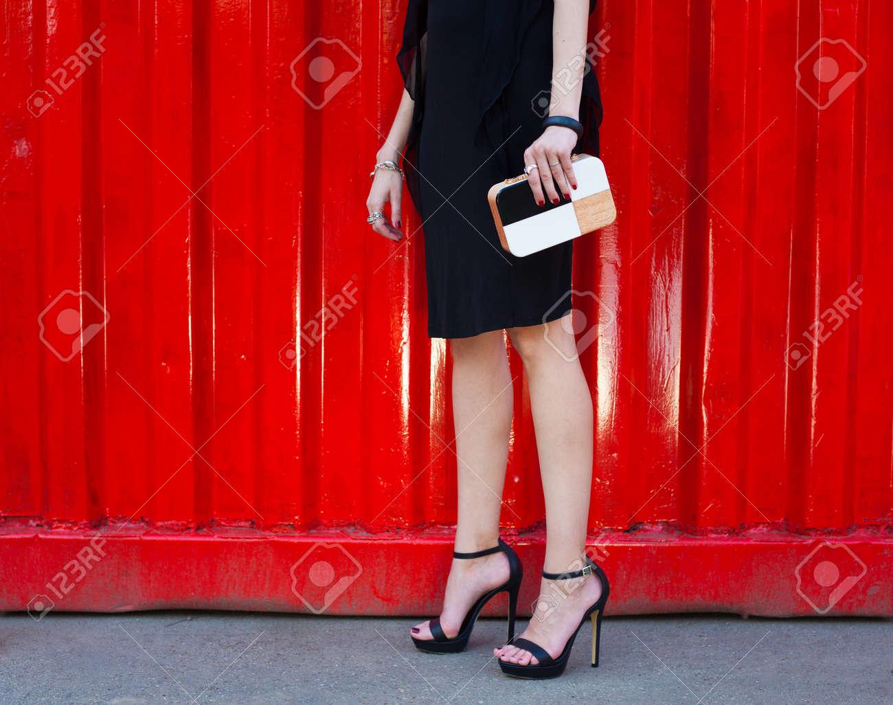 1f4755cda3e Fille Avec De Longues Jambes Dans Une Courte Robe Noire Et à La Mode Des  Chaussures Noires à Talons Hauts Debout Sur Un Fond Rouge Avec Un Embrayage  à La ...
