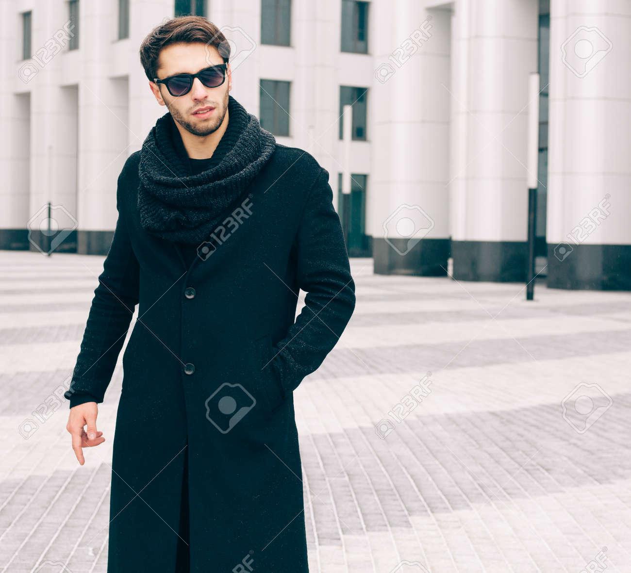 plus récent artisanat de qualité vêtements de sport de performance Mode et Style. Un jeune homme en manteau noir à la mode, lunettes de soleil  et snood posant sur la rue des affaires. De plein air.