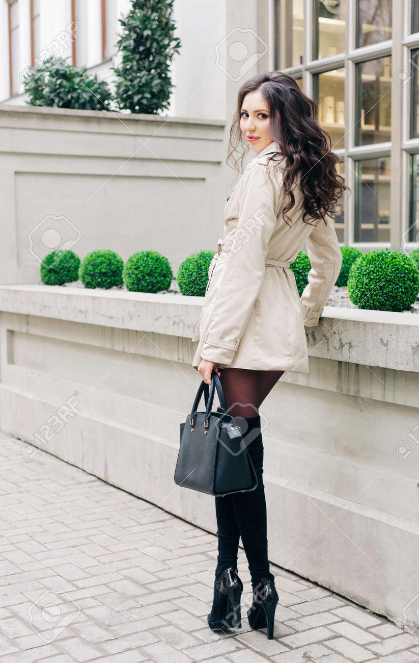Increíble Chica Morena De Largas Piernas Con El Pelo Largo Vestido Con Un Impermeable Botas Altas Negras Con Tacones Con Un Bolso Mirando A Su