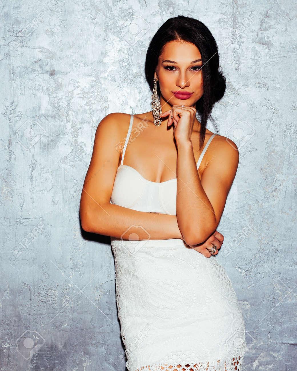 83403bf57a12 Belleza. Moda. Cuidado del cabello. Productos cosméticos. Mujer morena  joven atractiva arrogante hermosa que presenta en vestido blanco de moda en  un ...