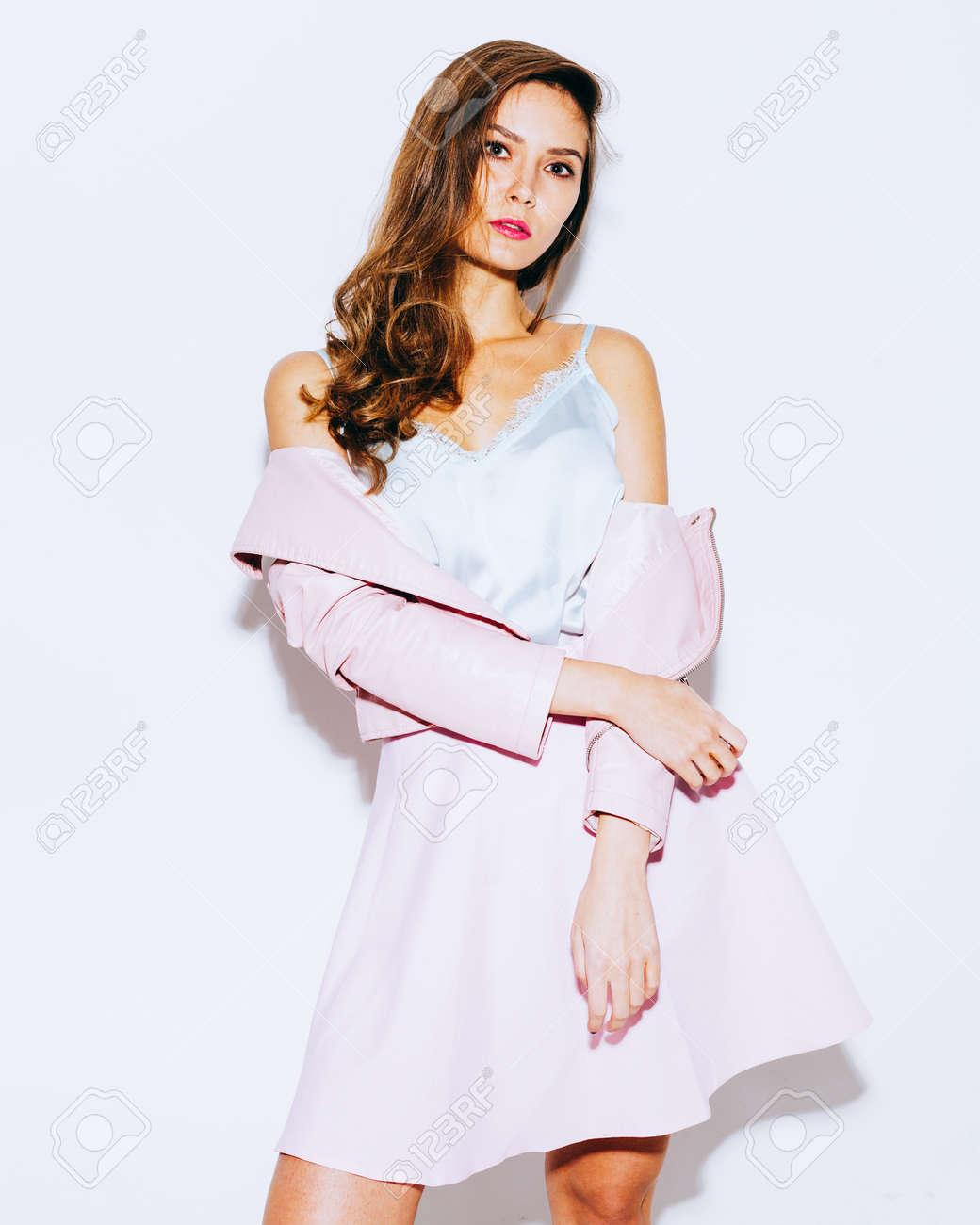 21111dd8e44002 Incroyablement belle fille brune posant dans une veste et une jupe rose à  la mode. Tenue légère de l'été. Sur fond blanc en studio.