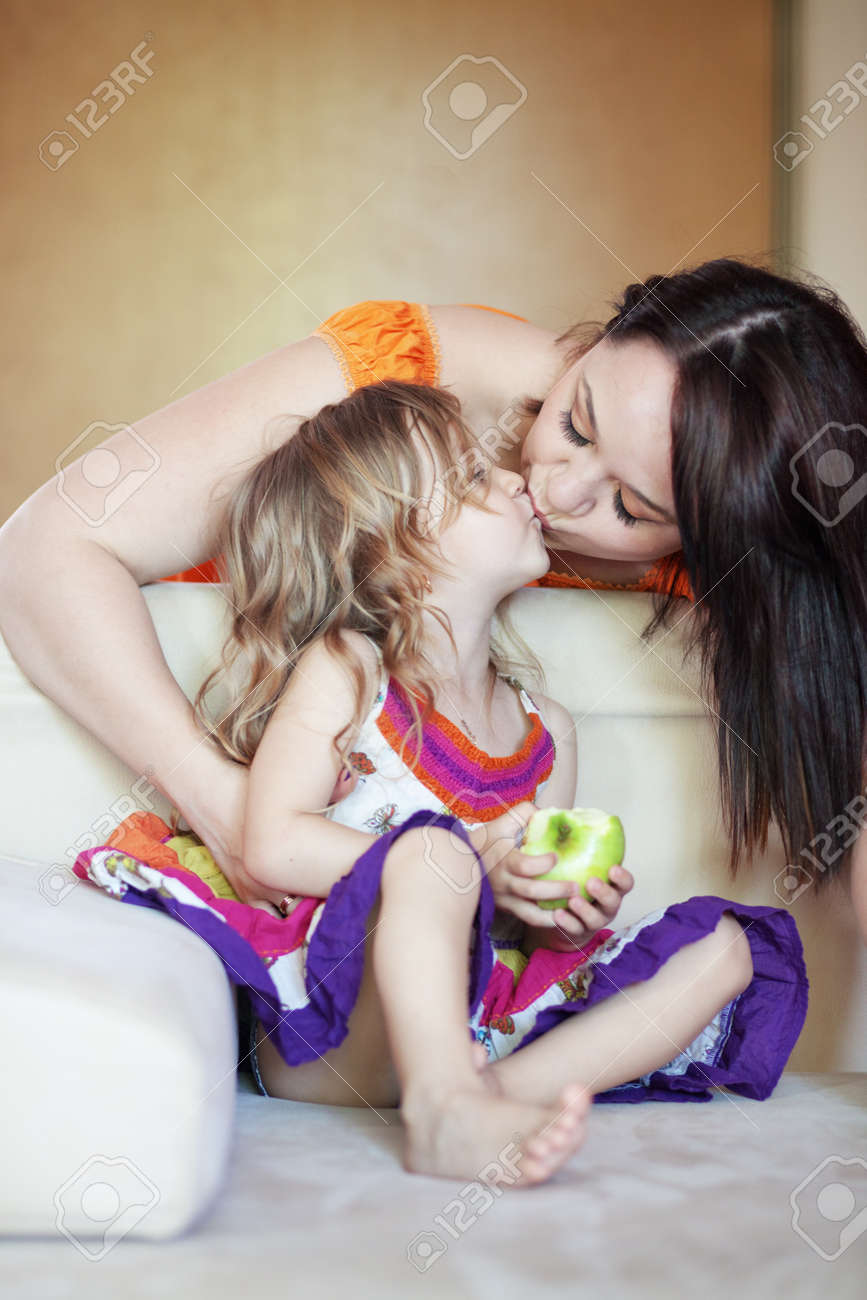 Mother with her small daughter playing on the sofa at home Stock Photo - 13559862