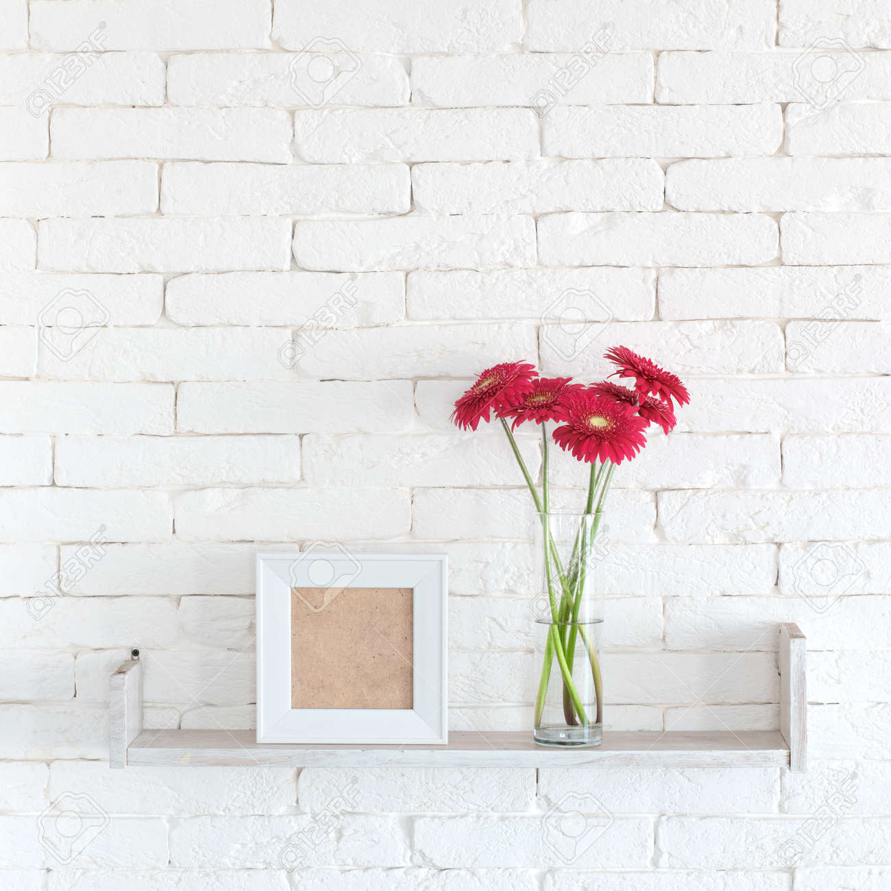 decorative shelf on white brick wall with flowers in vase on it stock photo