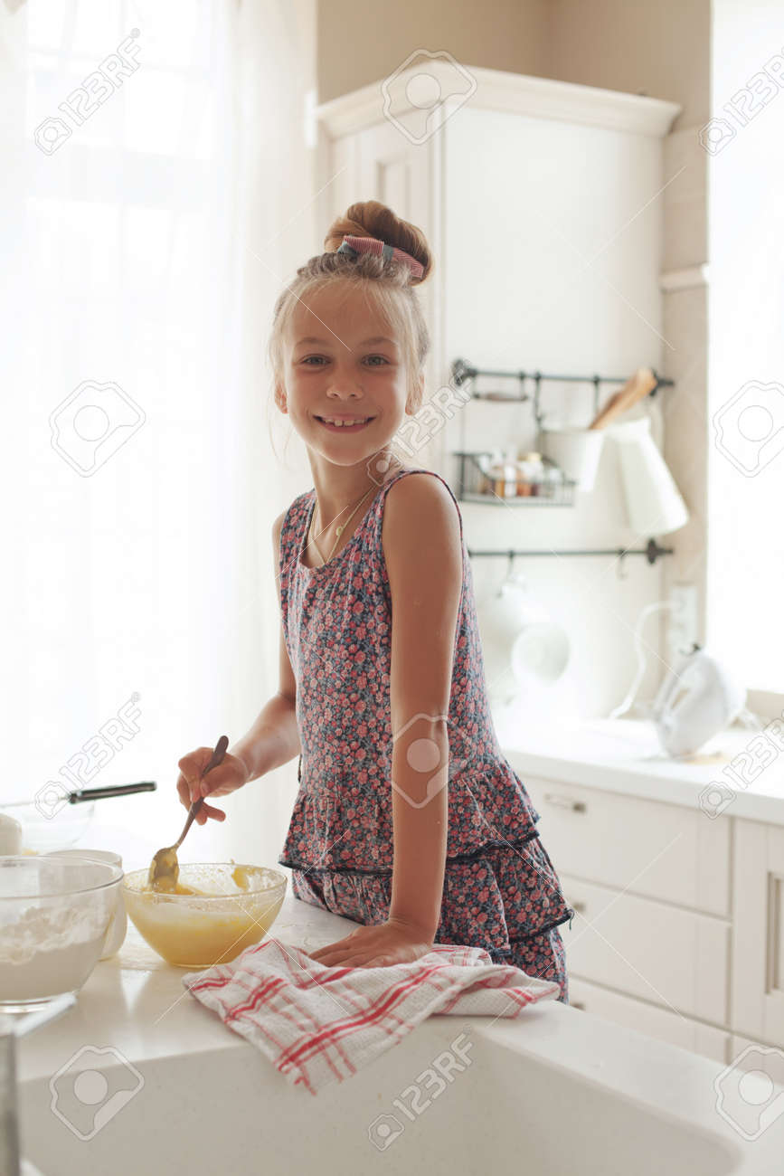 7 years old school girl cooking at the kitchen, casual lifestyle photo series Stock Photo - 29005494