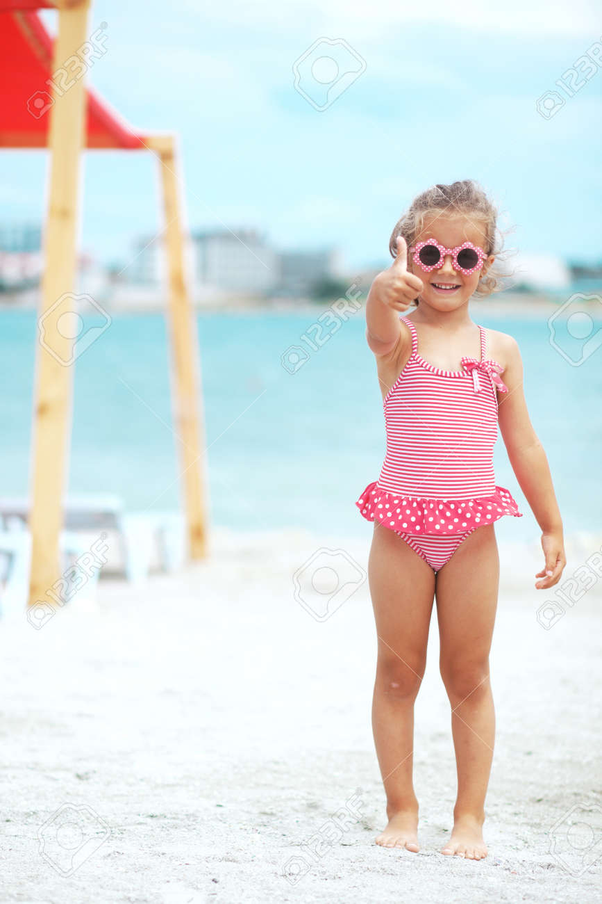 12453910341b3 Fashion 4 years old child wearing red swimsuit resting at beach in summer  Stock Photo -