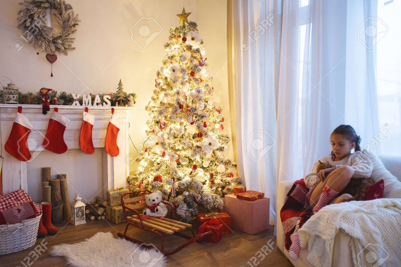 child sitting near decorated christmas tree and fireplace