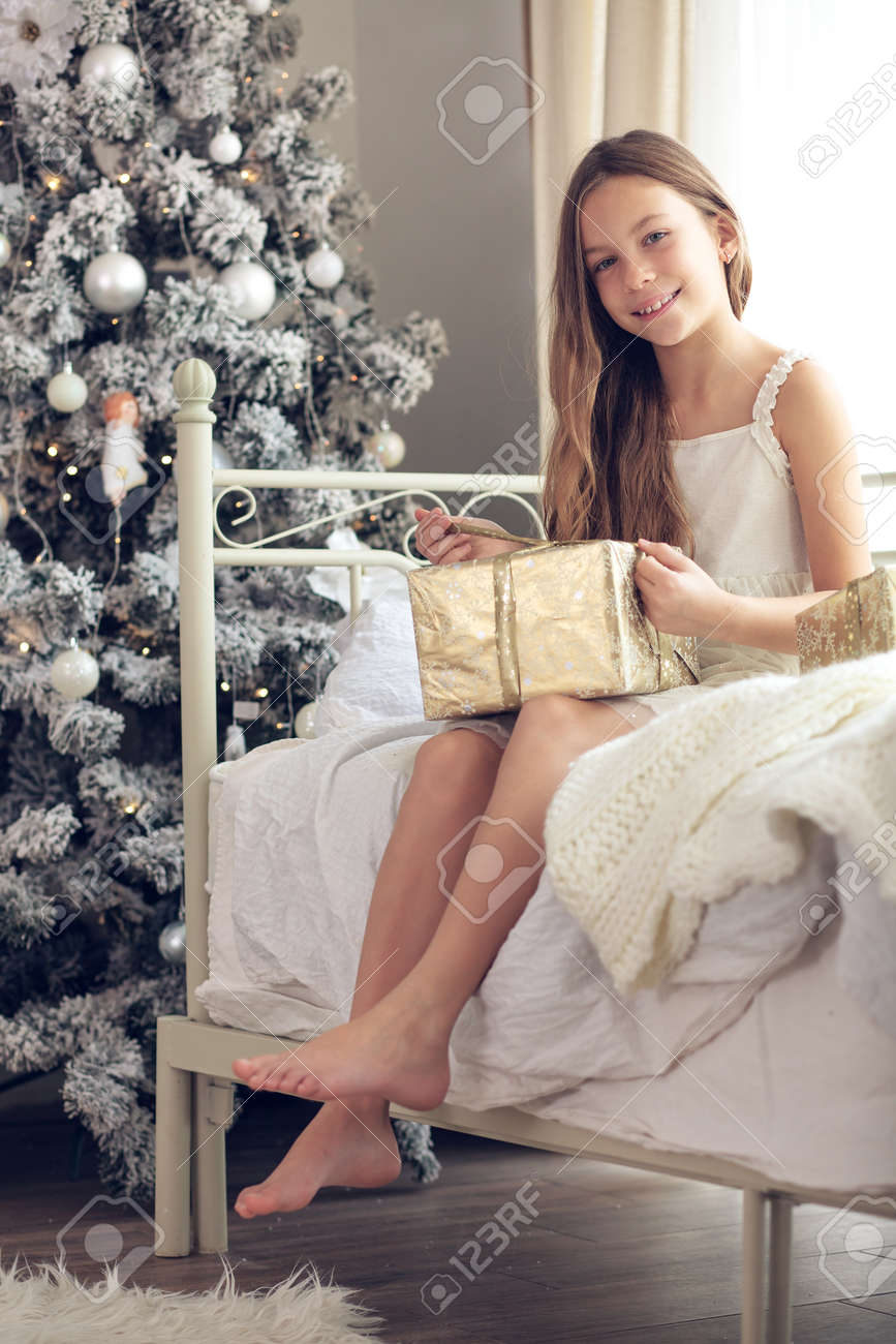 preteen in stockings Preteen child girl wake up in her bed near decorated Christmas tree in  beautiful hotel room