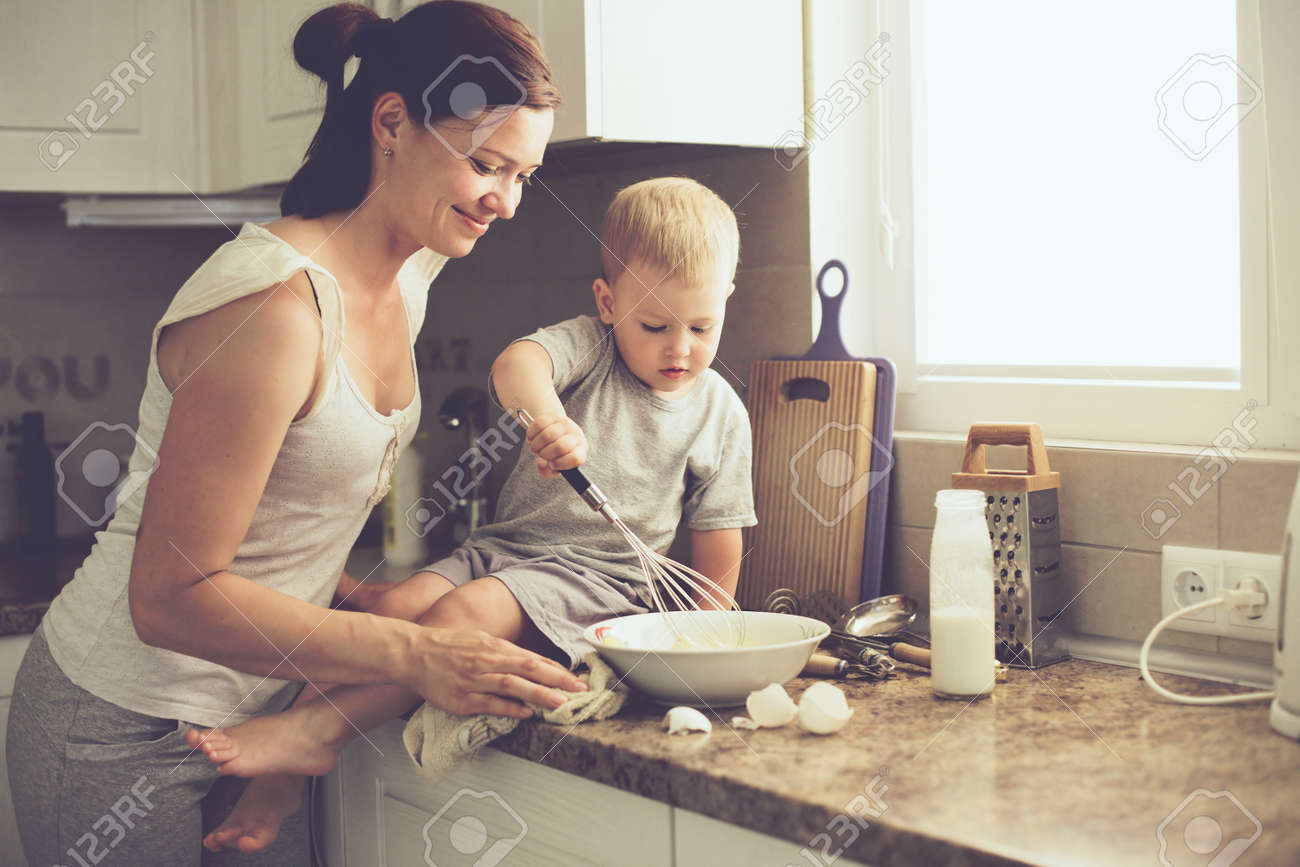 Mom with her 2 years old child cooking holiday pie in the kitchen to Mothers day, casual lifestyle photo series in real life interior - 41178672