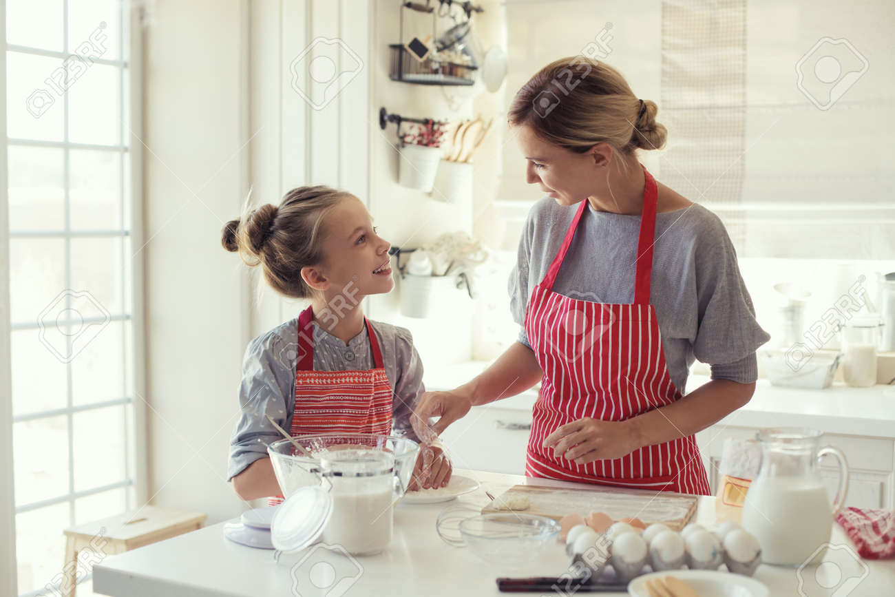 Mom with her 9 years old daughter are cooking in the kitchen to Mothers day, lifestyle photo series in bright home interior - 44715931