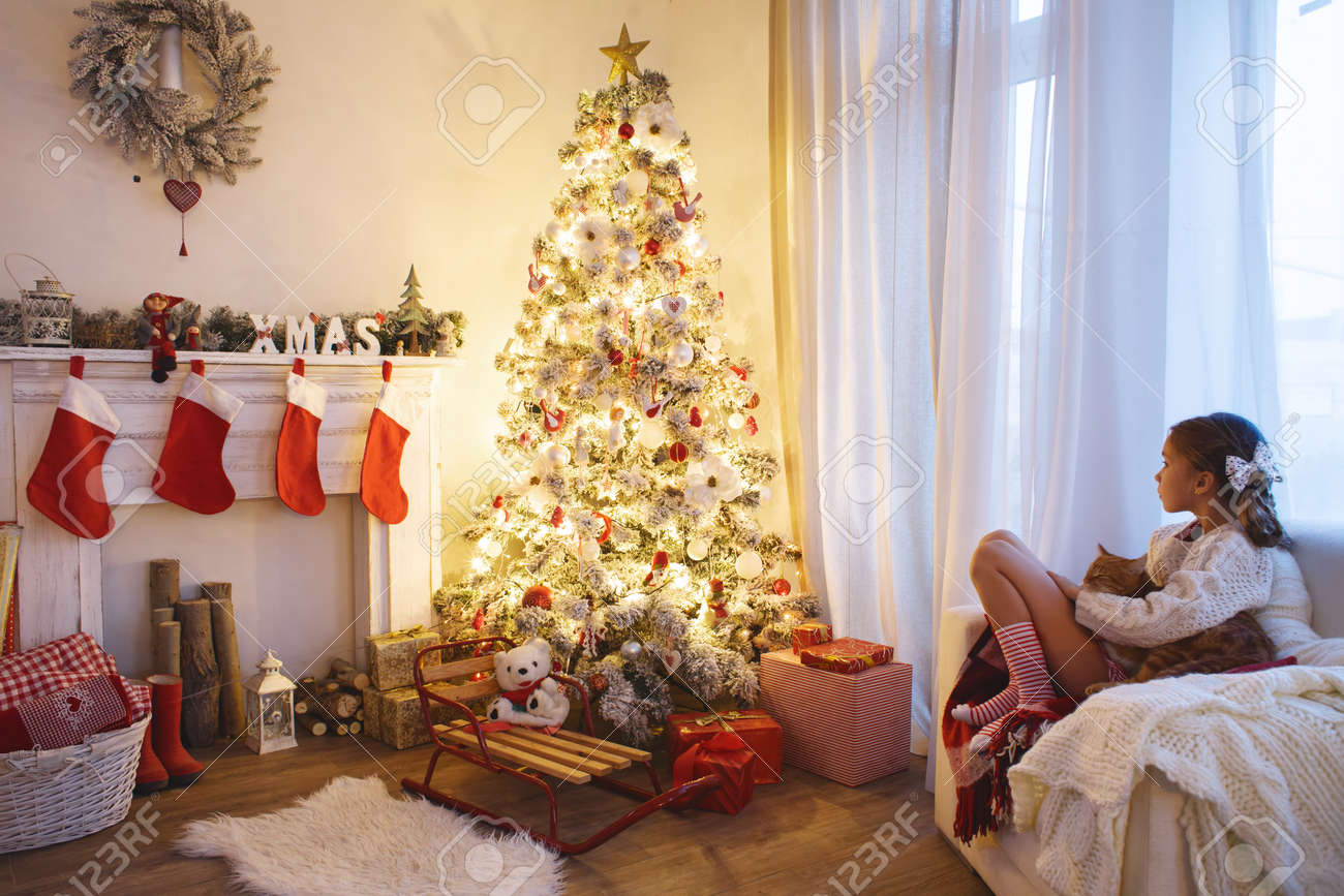 fille enfant assis près de l'arbre de noël décoré et cheminée dans