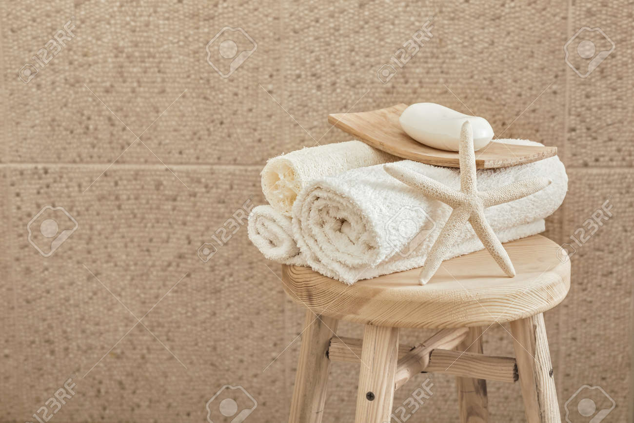 hotel bathroom decor closeup. white towels, soap, loofah and