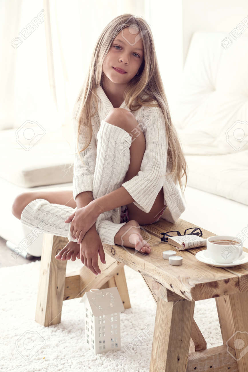 preteen in stockings model in woolen pullover: Preteen girl wearing warm knitted clothing is  sitting on rustic chair