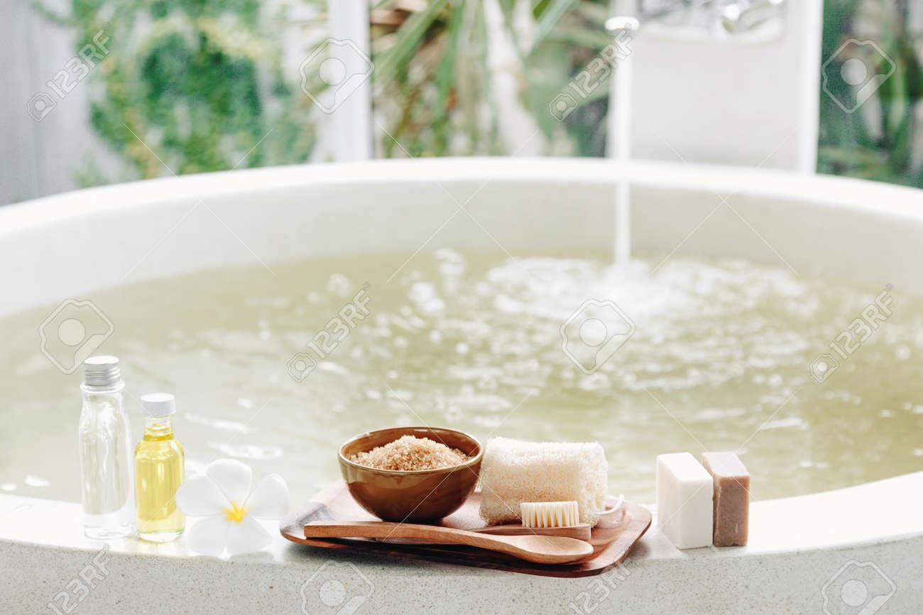 Spa decoration, natural organic products on a bathtube. Loofah, towel and frangipani flower - 54740902
