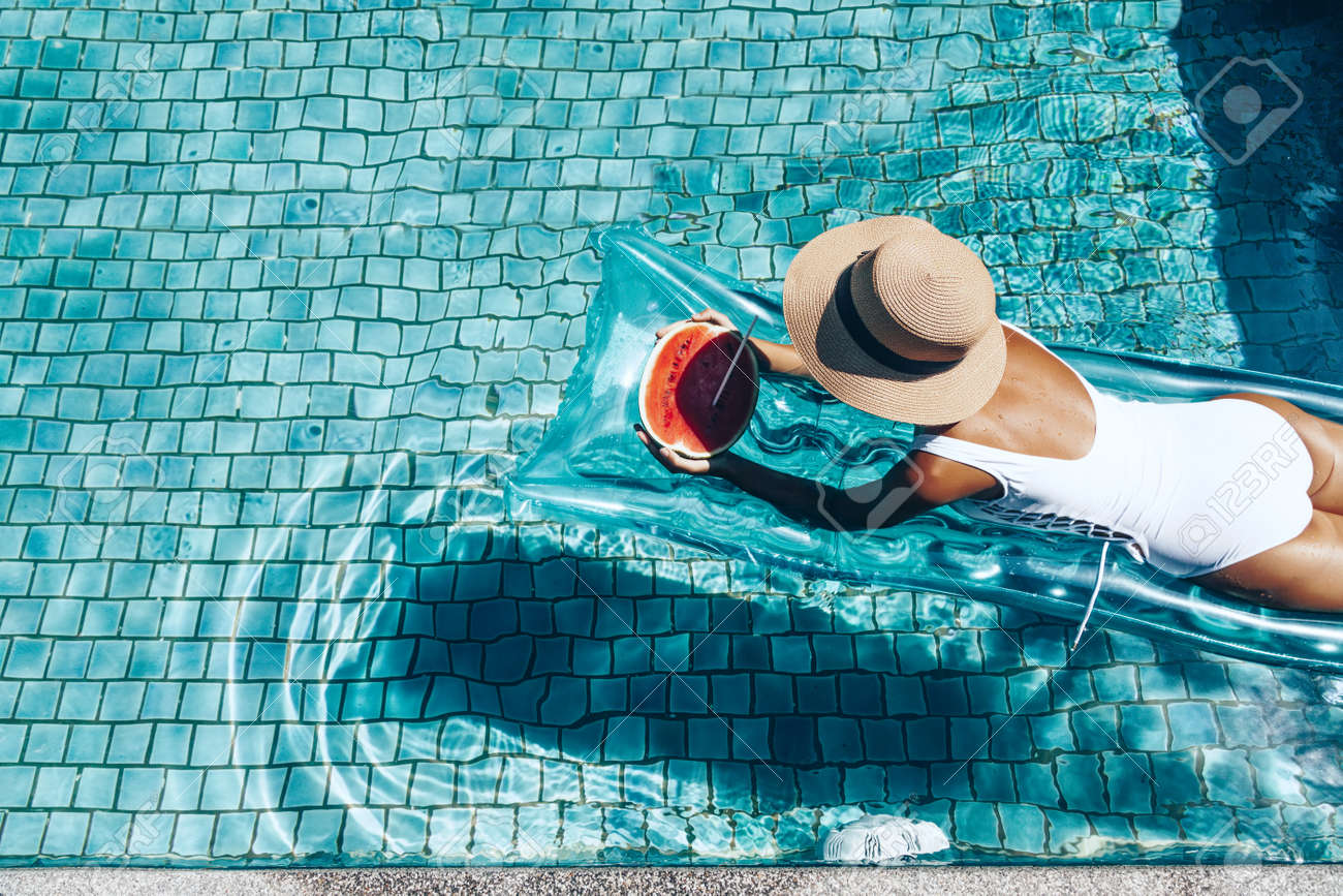 Girl floating on beach mattress and eating watermelon in the blue pool. Tropical fruit diet. Summer holiday idyllic. Top view. - 53244188