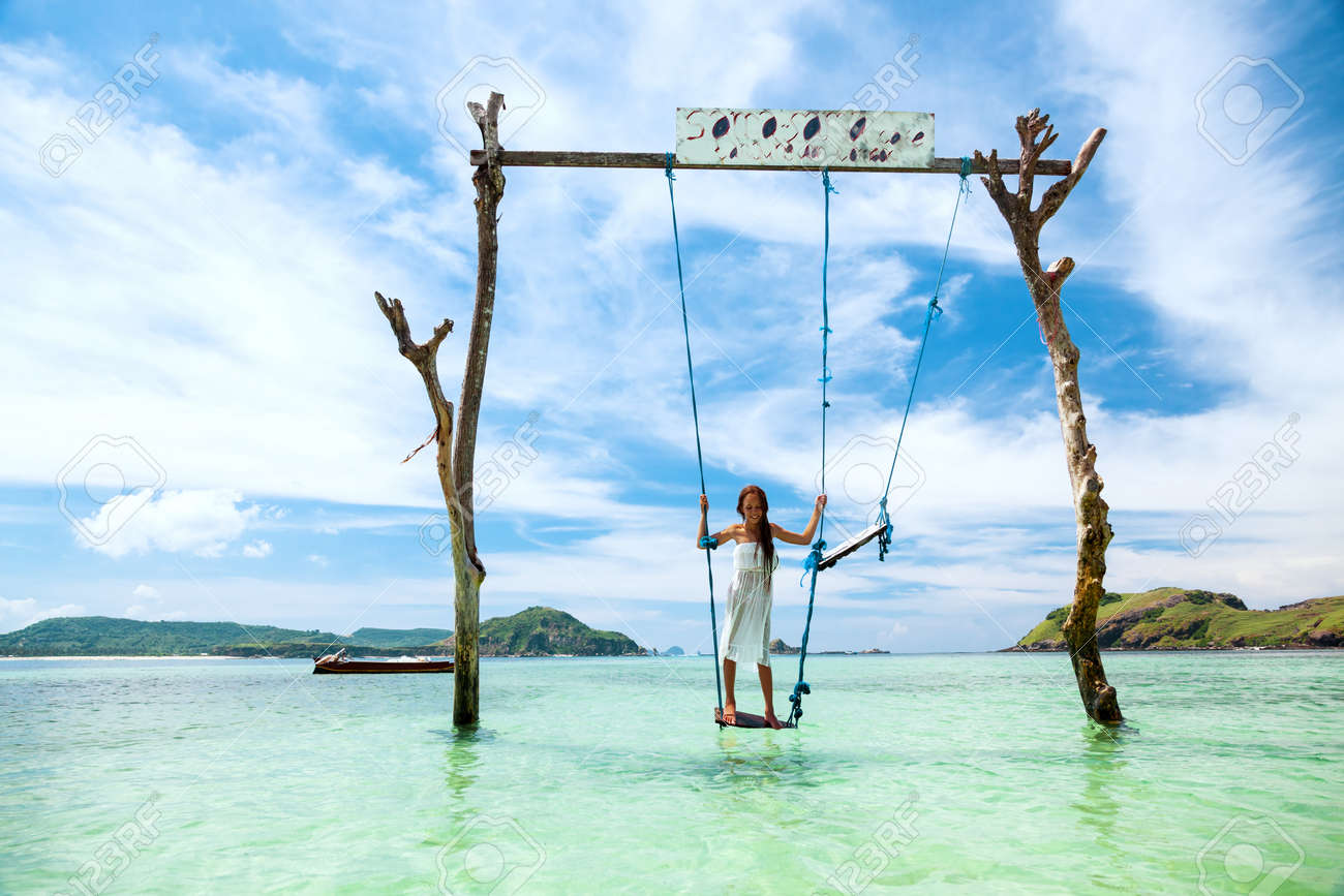 Girl swinging at tropical beach, sunny day, good weather. Swinging in  paradise island
